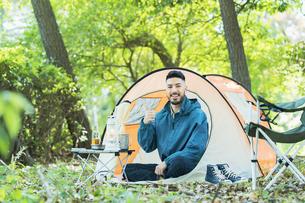 テントの前で笑顔でポーズする男性の写真素材 [FYI04852614]