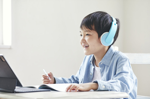 ヘッドホンをしながらタブレット端末で勉強する男の子の写真素材 [FYI04852663]