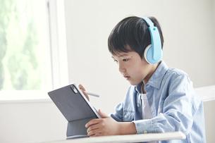 ヘッドホンをしながらタブレット端末で勉強する男の子の写真素材 [FYI04852672]
