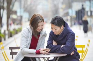 座ってスマートフォンを見るカップルの写真素材 [FYI04852686]