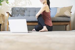 パソコンの画面を見ながらヨガをする女性の写真素材 [FYI04853394]