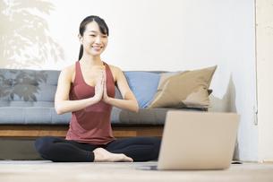 パソコンの画面を見ながらヨガをする女性の写真素材 [FYI04853402]