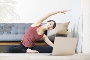 パソコンの画面を見ながらヨガをする女性の写真素材 [FYI04853403]