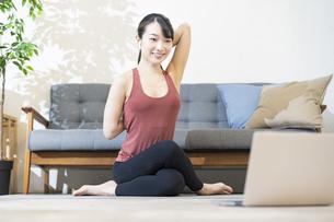 パソコンの画面を見ながらヨガをする女性の写真素材 [FYI04853404]