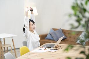 カジュアルな空間での仕事中にストレッチする女性の写真素材 [FYI04854483]