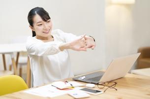 カジュアルな空間での仕事中にストレッチする女性の写真素材 [FYI04854486]