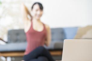 ノートパソコンの画面を見ながらヨガをする女性(ピントはパソコンに合わせています)の写真素材 [FYI04854489]