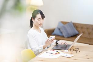 スマートフォンとノートパソコンを使って仕事するビジネスウーマンの写真素材 [FYI04854878]