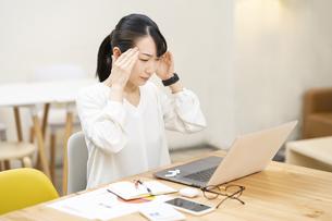仕事中、頭痛に悩む女性の写真素材 [FYI04854882]