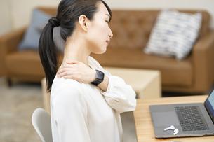 仕事中に肩こりを気にする女性の写真素材 [FYI04854886]