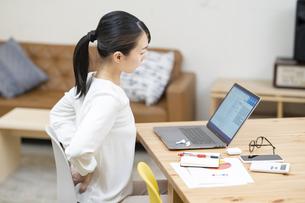 仕事中、腰痛に悩む女性の写真素材 [FYI04854888]