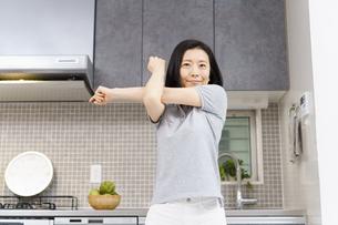 自宅の部屋で軽い運動をする中年女性の写真素材 [FYI04854890]