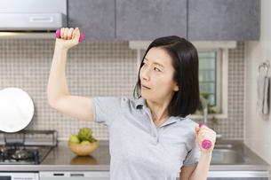 自宅の部屋で軽いダンベルをあげる運動をする中年女性の写真素材 [FYI04854893]