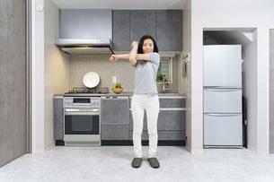 自宅の部屋で軽い運動をする中年女性の写真素材 [FYI04854903]