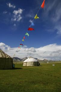 遊牧民の伝統的住居ユルトと風になびくカラフルな旗の写真素材 [FYI04854925]