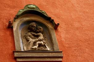 ヨーロッパの古民家の外壁に埋め込まれた宗教的オブジェの写真素材 [FYI04854930]