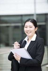 ノートを持って笑っているスーツ姿の女性の写真素材 [FYI04855414]
