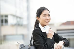 スマホを持って笑っているスーツ姿の女性の写真素材 [FYI04855607]