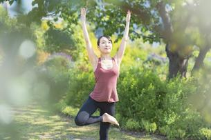緑あふれる公園でヨガをする若い女性の写真素材 [FYI04855793]