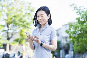 屋外でスマートフォンを操作する中年女性の写真素材 [FYI04855841]