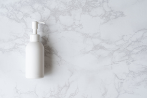 大理石のテーブルに置かれた白いボトルの写真素材 [FYI04855908]