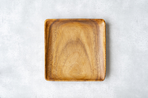 グレーの背景に置かれた木製で四角形の皿の写真素材 [FYI04855920]
