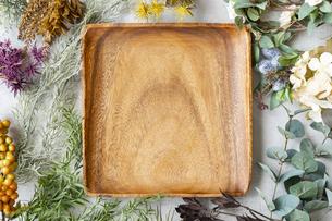 大理石のテーブルの上にセットされた木製のお皿と植物で作られた装飾物の写真素材 [FYI04855921]