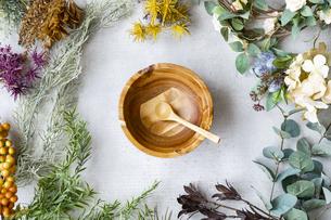 大理石のテーブルの上にセットされた木製のお皿と植物で作られた装飾物の写真素材 [FYI04855923]
