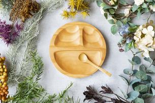 大理石のテーブルの上にセットされた木製のお皿と植物で作られた装飾物の写真素材 [FYI04855924]