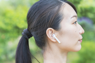 ワイヤレスイヤホンを装着した女性の横顔の写真素材 [FYI04856131]