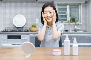 自宅で肌の状態を確かめる中年女性の写真素材 [FYI04856141]