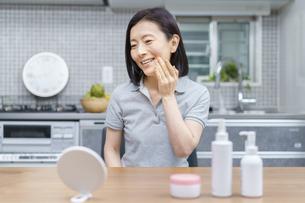 自宅で肌の状態を確かめる中年女性の写真素材 [FYI04856142]