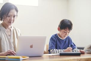 リビングで勉強する男の子とノートパソコンを使う女性の写真素材 [FYI04856335]