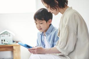 部屋でタブレットPCを見る女性と男の子の写真素材 [FYI04856336]