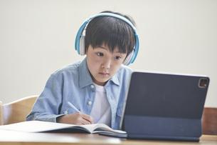 リビングでタブレットPCを見ながら勉強する男の子の写真素材 [FYI04856340]