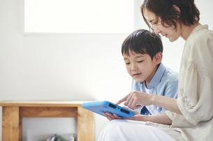 部屋でタブレットPCを見る女性と男の子の写真素材 [FYI04856342]