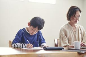 リビングで勉強する男の子とノートパソコンを使う女性の写真素材 [FYI04856348]