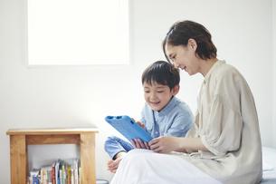 部屋でタブレットPCを見る女性と男の子の写真素材 [FYI04856356]