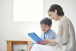 部屋でタブレットPCを見る女性と男の子の写真素材 [FYI04856359]
