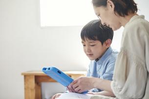 部屋でタブレットPCを見る女性と男の子の写真素材 [FYI04856360]