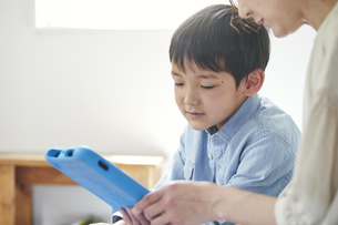 部屋でタブレットPCを見る女性と男の子の写真素材 [FYI04856363]