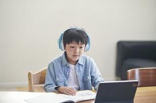 リビングでタブレットPCを見ながら勉強する男の子の写真素材 [FYI04856364]