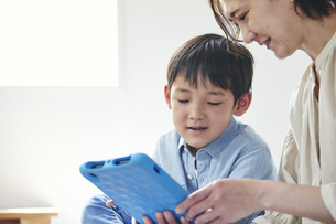 部屋でタブレットPCを見る女性と男の子の写真素材 [FYI04856365]
