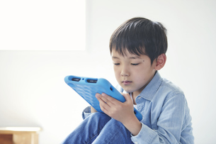 部屋でタブレットPCを見る男の子の写真素材 [FYI04856369]