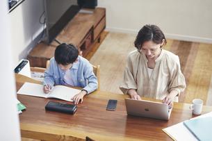 リビングで勉強する男の子とノートパソコンを使う女性の写真素材 [FYI04856371]