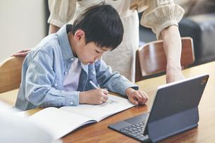 リビングでタブレットPCを見ながら勉強する男の子と女性の写真素材 [FYI04856374]