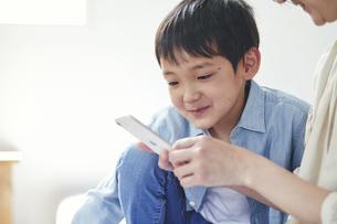 部屋でスマートフォンを見る女性と男の子の写真素材 [FYI04856378]