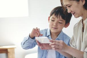 部屋でスマートフォンを見る女性と男の子の写真素材 [FYI04856488]