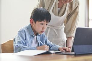 リビングでタブレットPCを見ながら勉強する男の子と女性の写真素材 [FYI04856495]