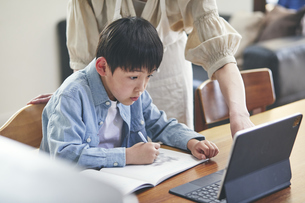リビングでタブレットPCを見ながら勉強する男の子と女性の写真素材 [FYI04856503]